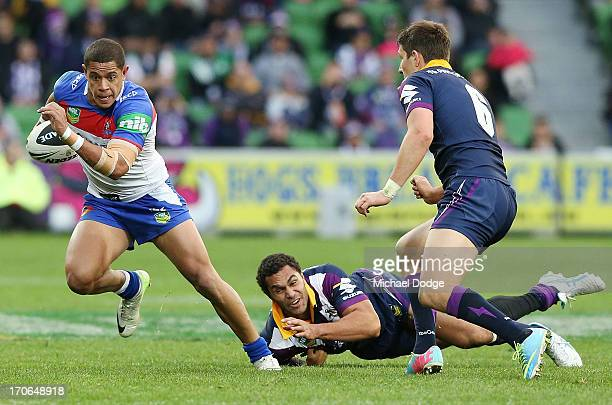Dane Gagai of the Knights runs with the ball past Justin O'Neill of the Storm during the round 14 NRL match between the Melbourne Storm and the...