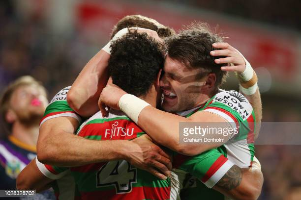 Dane Gagai of the Rabbitohs celebrates scoring a try with his teammates as Cameron Munster of the Storm looks dejected in the background during the...