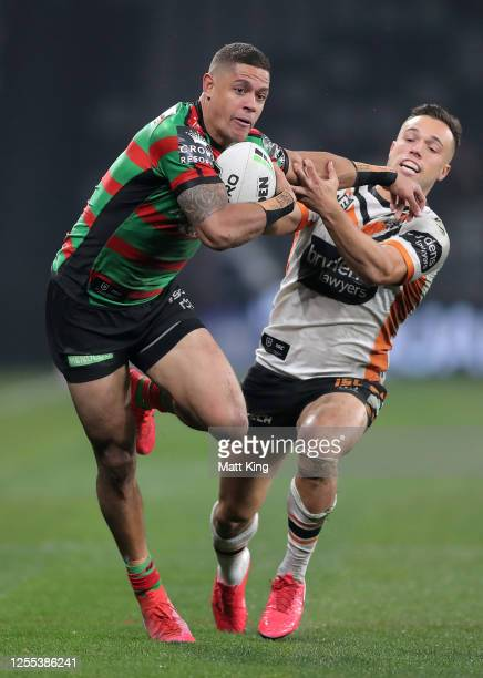 Dane Gagai of the Rabbitohs fends off a tackle by Luke Brooksof the Tigers during the round nine NRL match between the South Sydney Rabbitohs and...