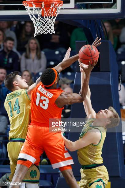 Dane Goodwin and Nate Laszewski of the Notre Dame Fighting Irish defend against Paschal Chukwu of the Syracuse Orange in the first half of the game...