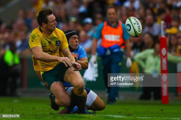 Dane HaylettPetty of Australia gets a pass away as he is tackled by Pietro Ceccarelli of Italy during the international rugby match between Australia...