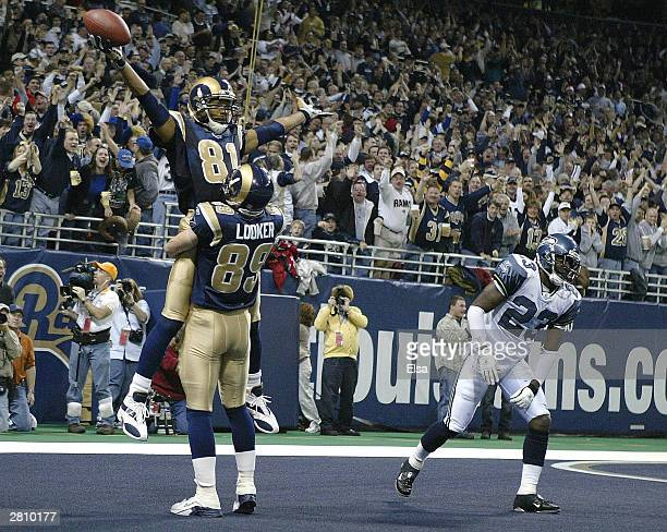 Dane Looker of the St Louis Rams lifts Torry Holt after Holt caught a touchdown pass in the second quarter against the Seattle Seahawks on December...