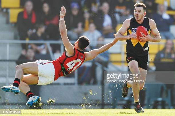 Dane Mcfarlane of Werribee runs with the ball past Ben McNeice of Essendon during the round 13 VFL match between Werribee and Essendon at Avalon...