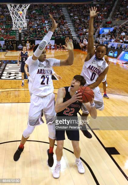 Dane Pineau of the St Mary's Gaels attempts a shot defended by Chance Comanche and Parker JacksonCartwright of the Arizona Wildcats during the second...