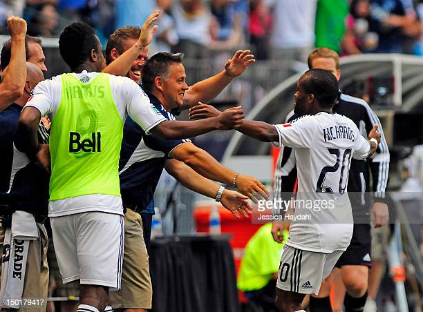 Dane Richards of the Vancouver Whitecaps celebrates his second half goal with teammates on the side line during their game against Real Salt Lake at...