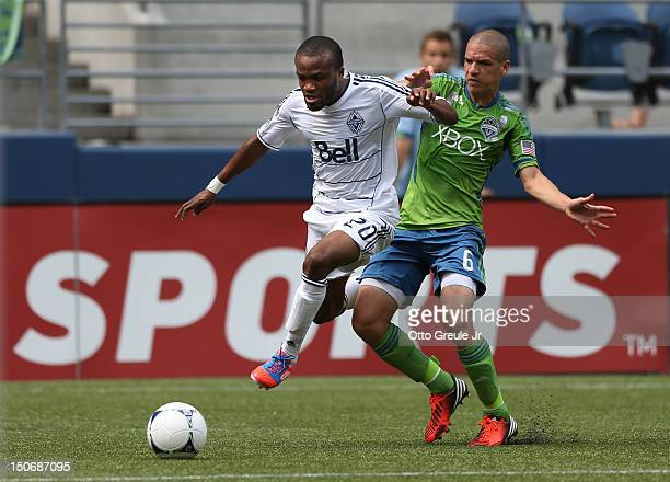 Dane Richards of the Vancouver Whitecaps dribbles against Osvaldo Alonso of the Seattle Sounders FC at CenturyLink Field on August 18 2012 in Seattle...
