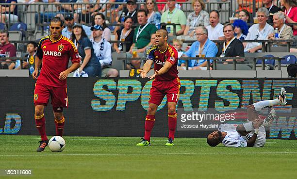 Dane Richards of the Vancouver Whitecaps grabs his ankle after a tackle from Chris Wingert of Real Salt lake while his teammate Fabian Espindola...