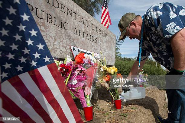 Dane Senser waters flowers at a makeshift memorial outside the Ronald Reagan Presidential Library as former first lady Nancy Reagan lies in repose on...