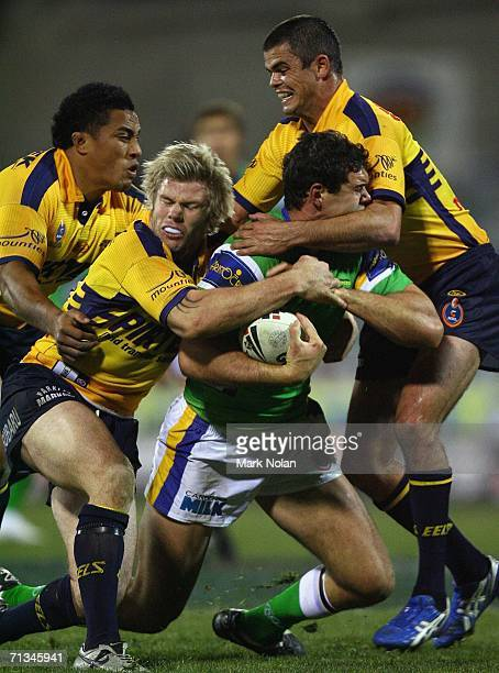 Dane Tilse of the Raiders is tackled by Fuifui Moimoi Glenn Morrison and Daniel Wagon of the Eels during the round 17 NRL match between the Canberra...