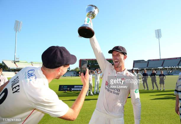 Dane Vilas of Lancashire lifts the Specsavers County Championship Division Two trophy as Tom Bailey takes a photograph after the Specsavers County...