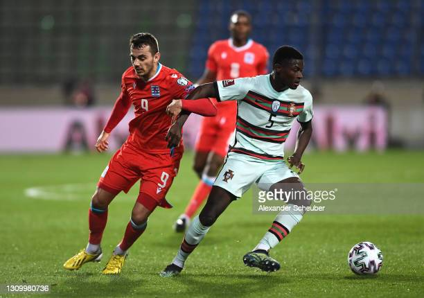 Danel Sinani of Luxembourg battles for possession with Nuno Mendes of Portugal during the FIFA World Cup 2022 Qatar qualifying match between...