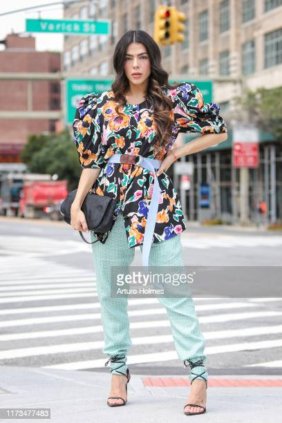 Danella Urbay is seen wearing floral print blouse blue belt green pants black heels and black Christian Dior purse during New York Fashion Week on...