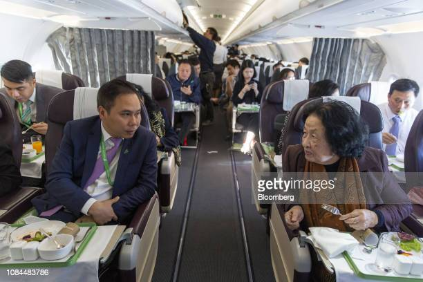 Dang Tat Thang deputy general director of FLC Group JSC and chief executive officer of Bamboo Airways left speaks to a passenger in the business...