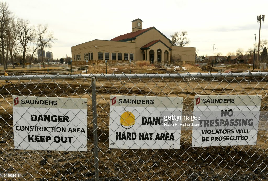 Danger and No Trespassing signs hang on a fence that closes