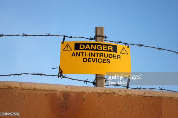 Danger, anti-intruder devices warning sign on a wall in London, England, United Kingdom