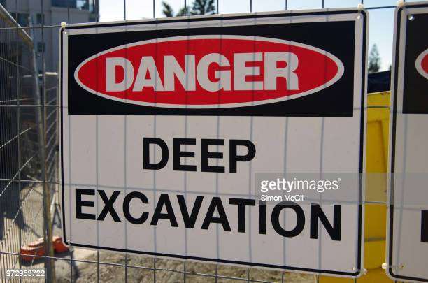 'Danger: Deep excavation' sign on a fence around a construction site