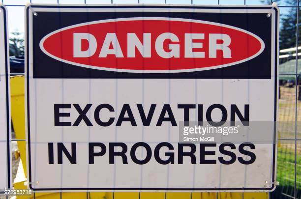 'Danger: Excavation in progress' sign on a fence around a construction site