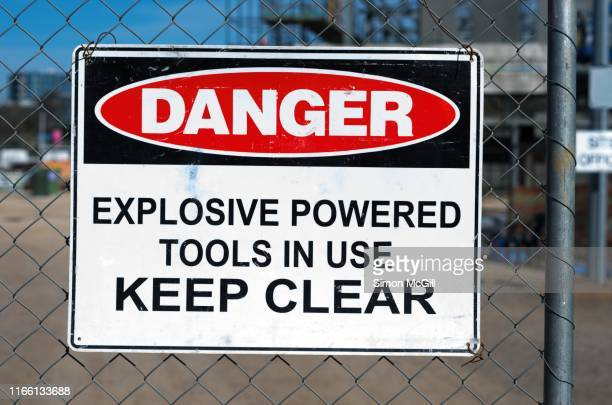 'danger: explosive powered tools in use. keep clear' warning sign on a wire mesh fence around a construction site - explosive stock pictures, royalty-free photos & images