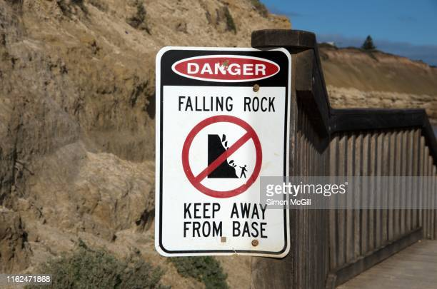 'danger: falling rock. keep away from base' warning sign at the bottom of cliffs - ウィランガ ストックフォトと画像