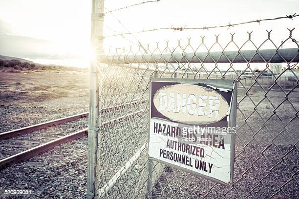 a danger, hazardous area sign on a fence near railroad tracks - robb reece stockfoto's en -beelden