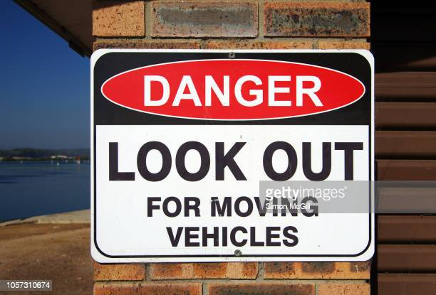 'danger: look out for moving vehicles' sign - car crash wall stock photos and pictures