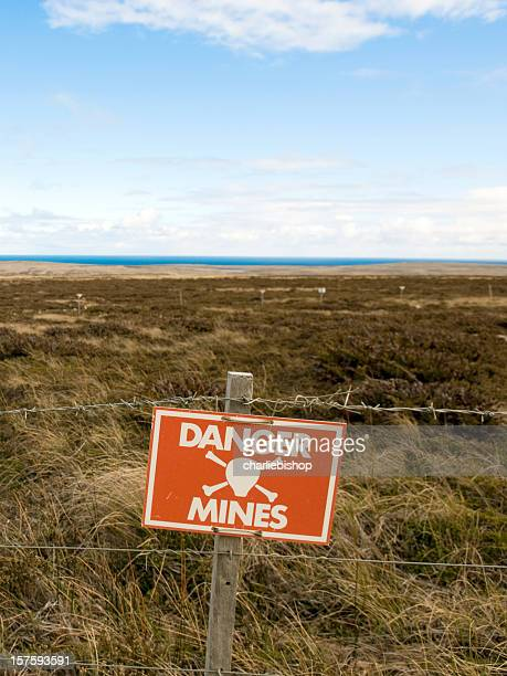 danger minefield with warning sign - land mine stock photos and pictures
