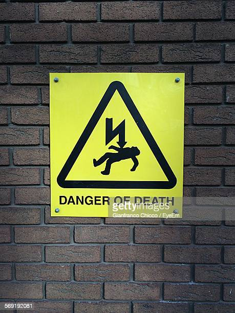 Danger of death sign board on brick wall
