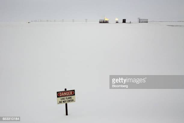A danger sign stands in front of gas flares outside the BP Plc Central Gas Facility in Prudhoe Bay Alaska US on Thursday Feb 16 2017 Four decades...