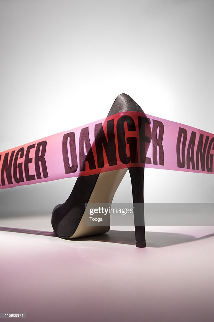 """Danger"" tape around stiletto heel : Stock Photo"