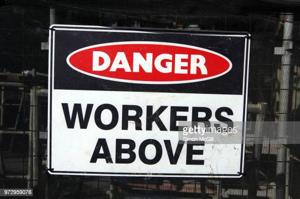'Danger: Workers above' sign on a fence around a construction site