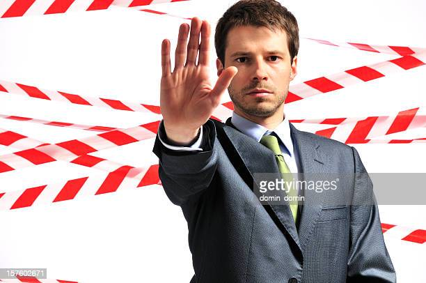 Danger zone, man against safety tape background, isolated, studio shot