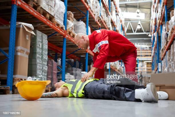 perigoso acidente durante o trabalho. paramédico dá primeiros socorros - socorrista - fotografias e filmes do acervo