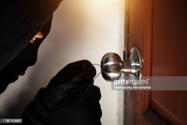 a dangerous burglar wearing a key into the victim's door,thieves - door lock stock pictures, royalty-free photos & images