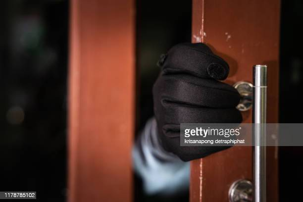 dangerous masked burglar with crowbar breaking into a victim's home door - burglar stock pictures, royalty-free photos & images