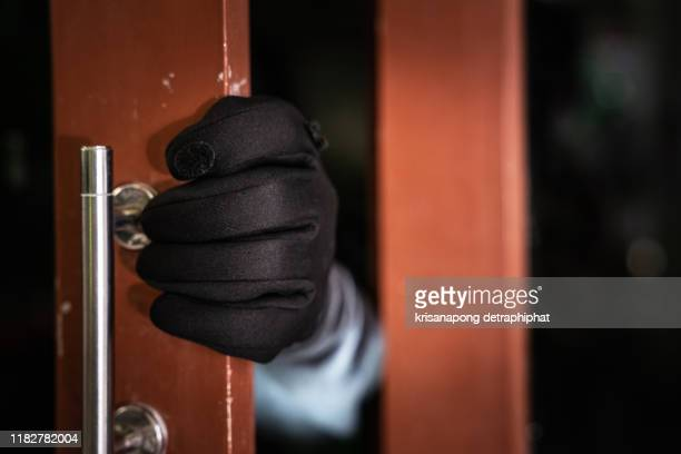 dangerous masked burglar with crowbar breaking into a victim's home door,home insurance concept - burglar stock pictures, royalty-free photos & images
