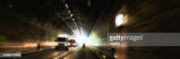 dangerous oncoming traffic inside a road tunnel - light at the end of the tunnel stock pictures, royalty-free photos & images