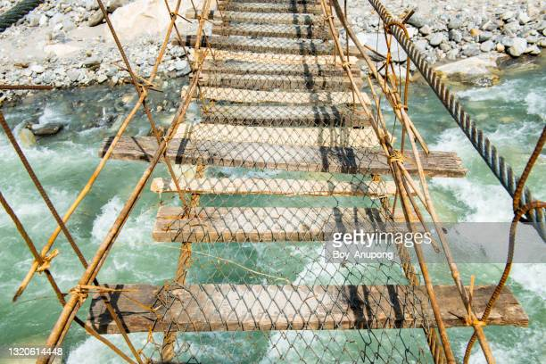 dangerous rope hanging bridge for crossing the river on the way to annapurna sanctuary in nepal. - danger stock pictures, royalty-free photos & images