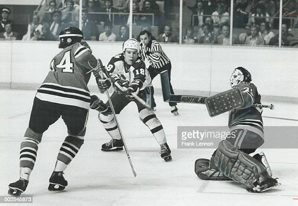 Dangerous territory Paul Gardner of Leafs tries to flip puck out of the air toward Chicago Black Hawks' goalie Tony Esposito right who comes out to...