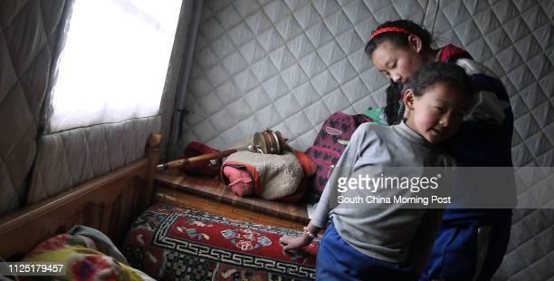 Dangqiu Lamao combs hair for her younger sister Zhuoga Yongji, 11 in their tent in the early morning in Jiegu, Yushu, Qinghai, April 15, 2011....