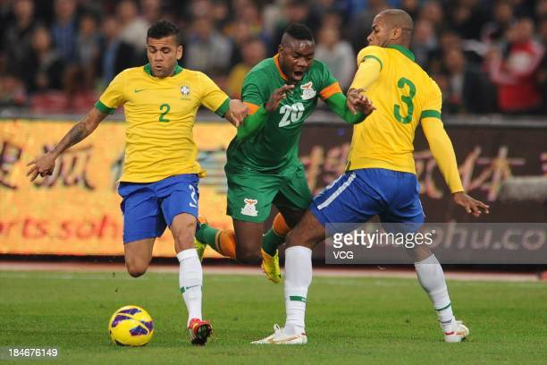 Dani Alves Dede of Brazil and Emmanuel Mayuka of Zambia battle for the ball during the international friendly match between Brazil and Zambia at...