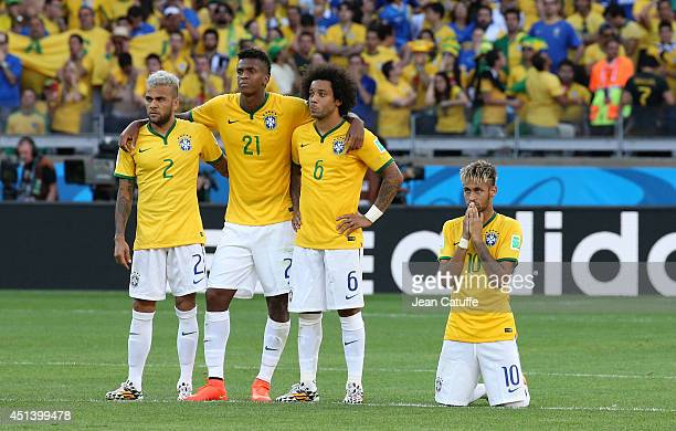 Dani Alves Jo Marcelo and Neymar of Brazil look on during the penalty shootout of the 2014 FIFA World Cup Brazil round of 16 match between Brazil and...