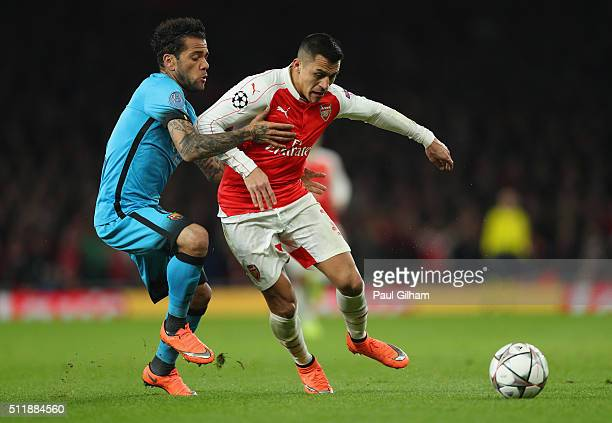 Dani Alves of Barcelona tackles Alexis Sanchez of Arsenal during the UEFA Champions League round of 16 first leg match between Arsenal and Barcelona...