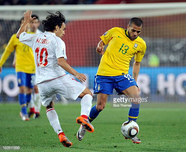 Dani Alves of Brazil challenged by Jorge Valdivia of Chile during the 2010 FIFA World Cup South Africa Round of Sixteen match between Brazil and...