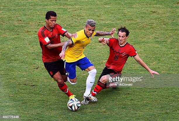 Dani Alves of Brazil is challenged by Giovani dos Santos and Andres Guardado of Mexico during the 2014 FIFA World Cup Brazil Group A match between...