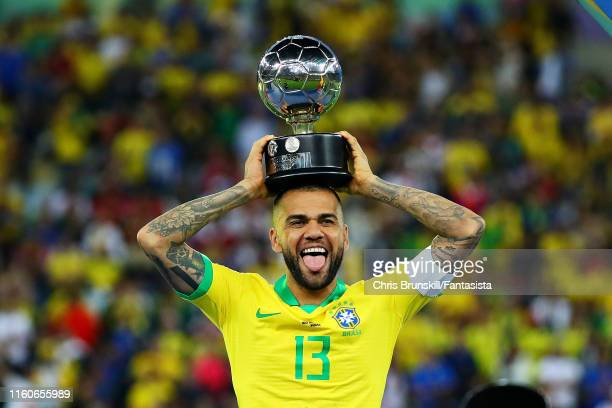 Dani Alves of Brazil is presented with the Player of the Tournament trophy after the Copa America Brazil 2019 Final match between Brazil and Peru at...
