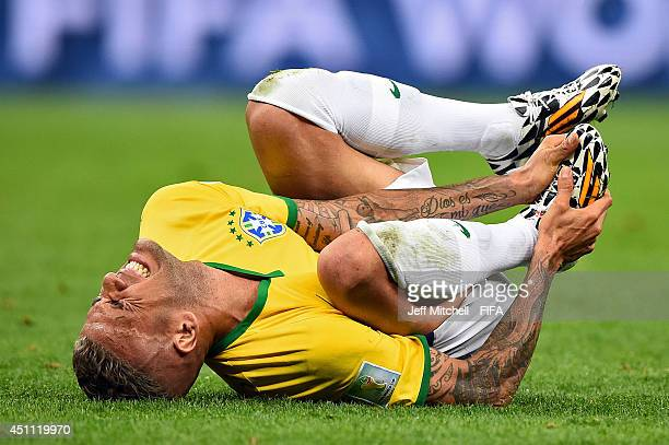 Dani Alves of Brazil lies on the field after a challenge during the 2014 FIFA World Cup Brazil Group A match between Cameroon and Brazil at Estadio...