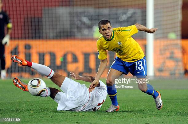 Dani Alves of Brazil tackles Jean Beausejour of Chile during the 2010 FIFA World Cup South Africa Round of Sixteen match between Brazil and Chile at...