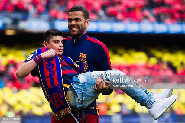 Dani Alves of FC Barcelona carries a disabled young supporter before the La Liga match between FC Barcelona and RCD Espanyol at Camp Nou on May 8...