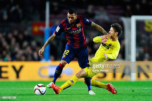 Dani Alves of FC Barcelona is brought down by Luciano Vietto of Villarreal CF during the Copa del Rey SemiFinal first leg match between FC Barcelona...