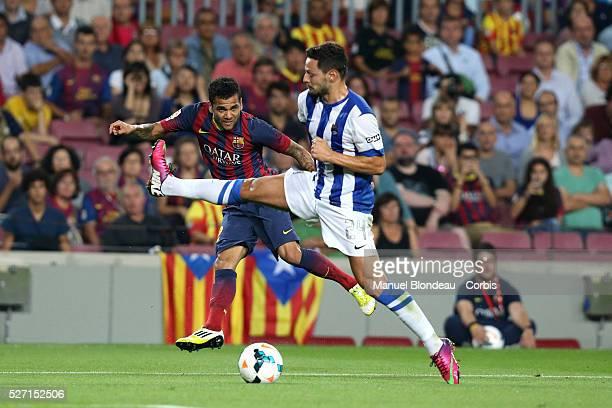 Dani Alves of FC Barcelona kicks the ball under pressure from Alberto de La Bella of Real Sociedad during the La Liga football match between FC...